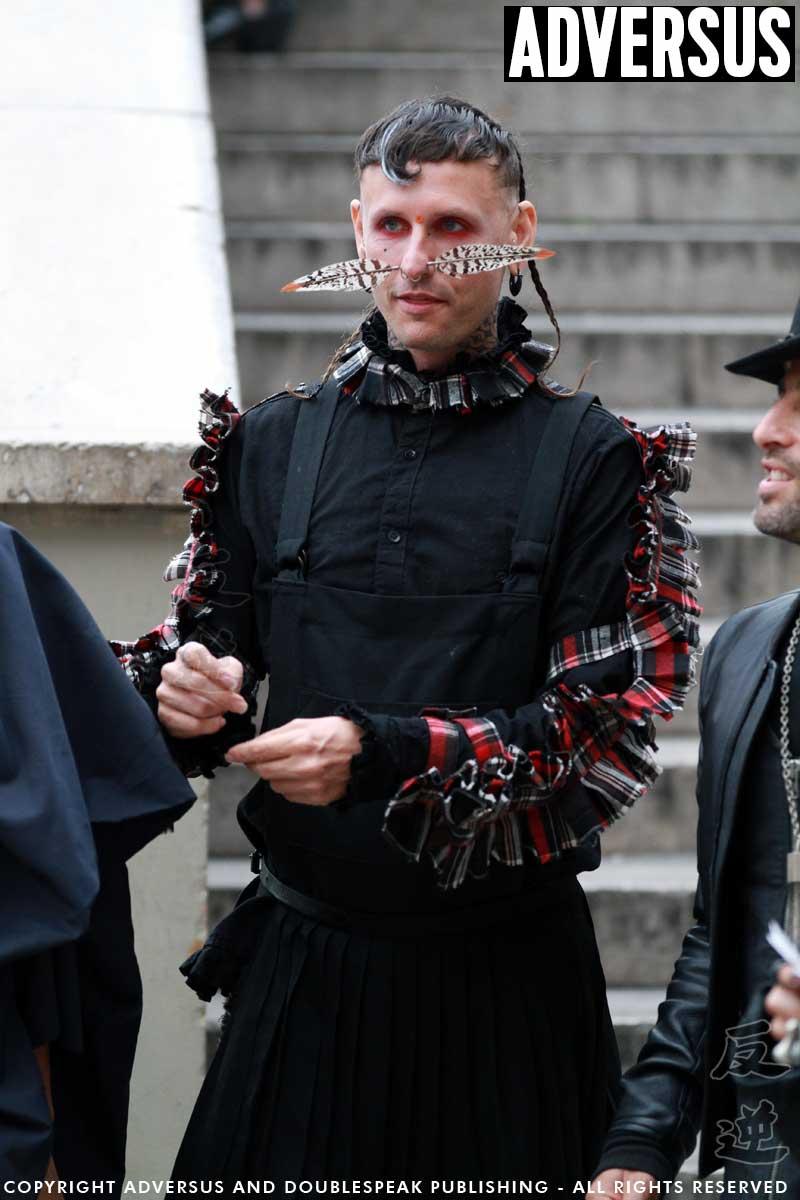 Street style uomo a Parigi. Penna d'uccello che trafigge il naso e gonnellona nera